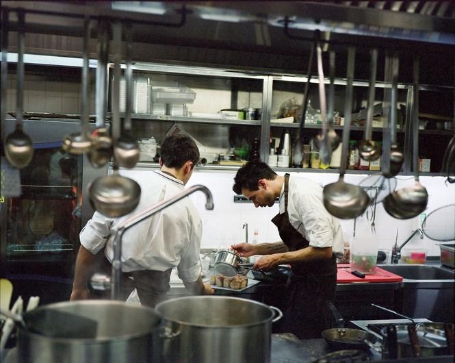 Итальянский шеф Лоренцо Кого с помощником поливают соусом брикеты из разных частей поросенка, доведенные до совершенной нежности многочасовым томлением