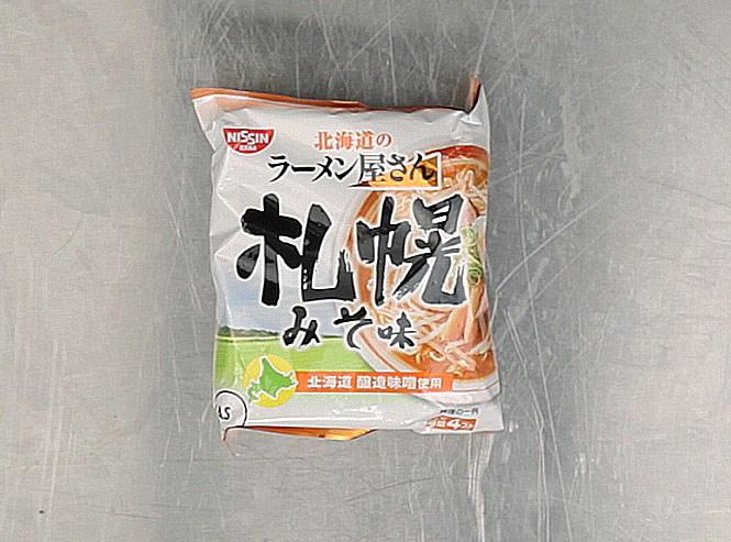 Лапша «Саппоро-мисо», сделана той самой пищевой японской корпорацией Nissin, которую создал Момофуку Андо. В состав действительно входит мисо — помимо заменителя сахара, неуточненных специй и приправ, лактозы, лука, гидролизатора белка, углекислого натрия, карбоната кальция, красителя, загустителя и витамина E. По идее, эту лапшу, как написано на пачке, нужно варить 3 минуты в кипящей воде, а потом добавлять все остальное — может, потому что мы ее заваривали, она и не произвела ни на кого особого впечатления.